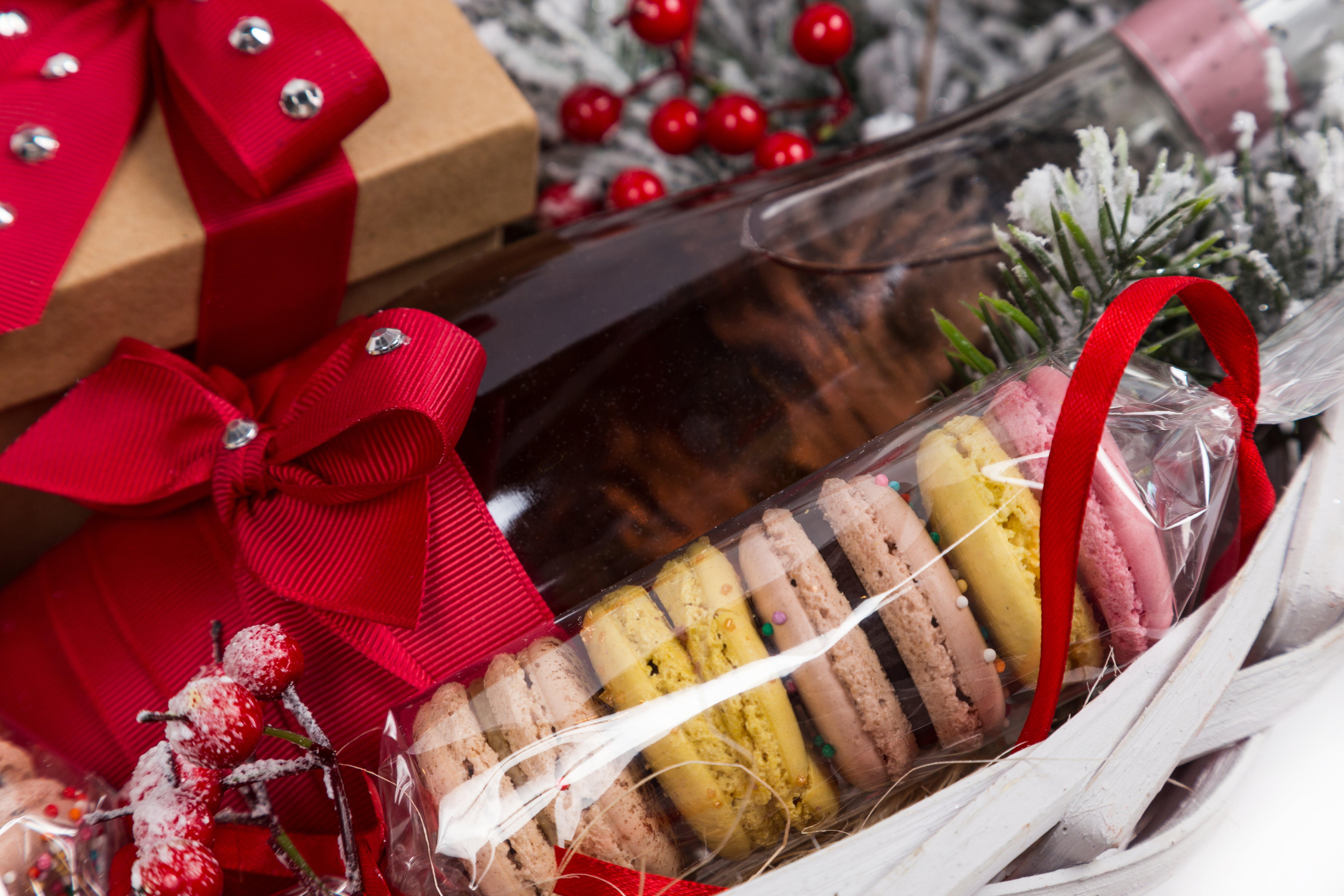 christmas present in basket with sweet pastry, bottle of wine and decor